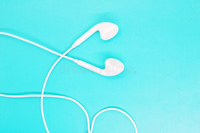 White headphones close up on a turquoise background, headphones for listening to music, modern gadgets, youth accessories stock images