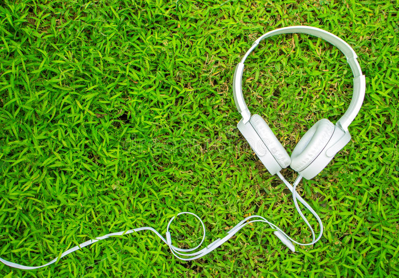 White headphones on green grass. Summer lawn with personal device. royalty free stock photos