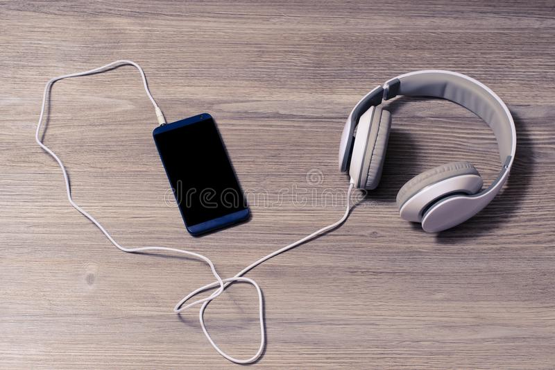 White headphones and mobile phone on a table hobby leisure rest relax free time hipster student earphones education studying conce royalty free stock image