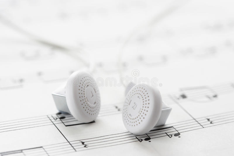 White headphones on sheet music royalty free stock photos