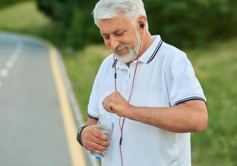 White-heared senior man opening water bottle during morning scamper. stock photography