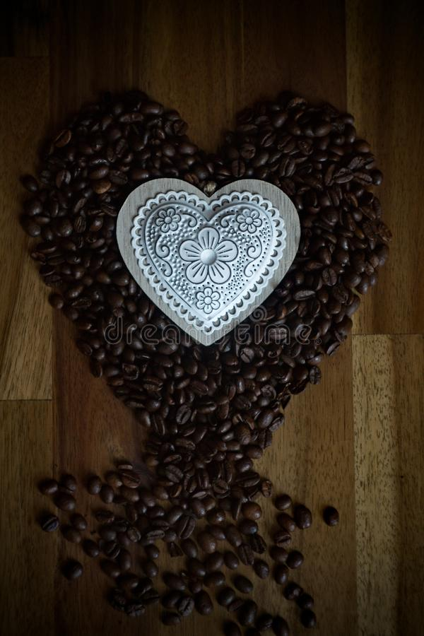 White heart and coffee beans on a wooden table royalty free stock photography