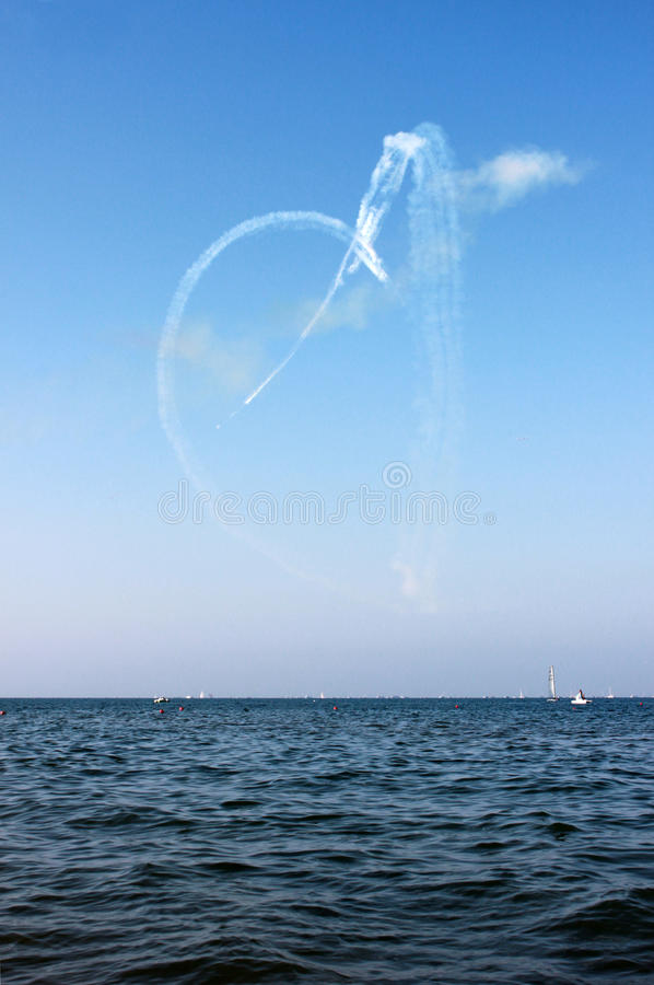 White heart drown by airplane and sea on the blue sky background, vertical view. stock image