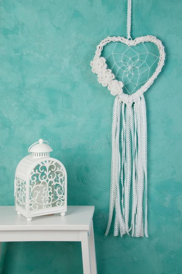 White heart dream catcher. White heart lace dream catcher and white candlestick on aquamarine textured background. Texture of concrete, copy space for text royalty free stock photo