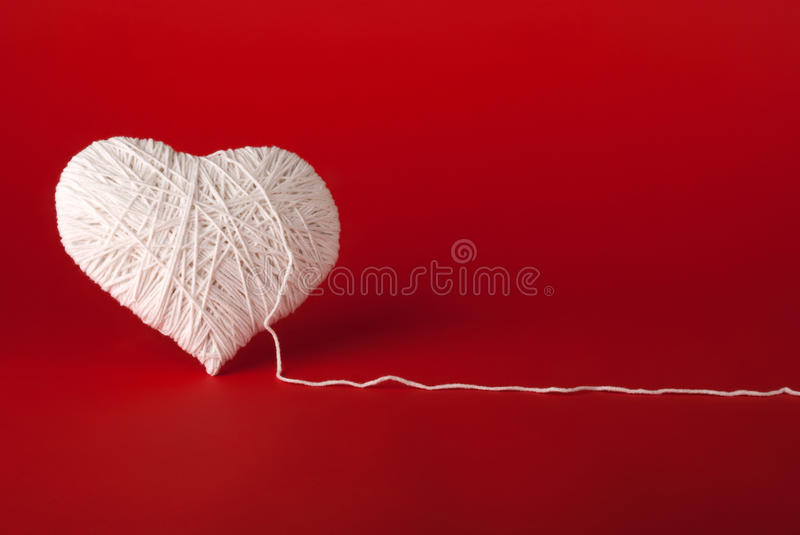 White heart made of wool on a red background royalty free stock images