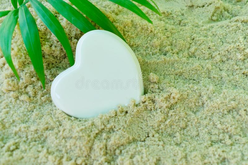 White heart and palm branch, lies on the sea sand. The concept of a summer holiday. royalty free stock photo