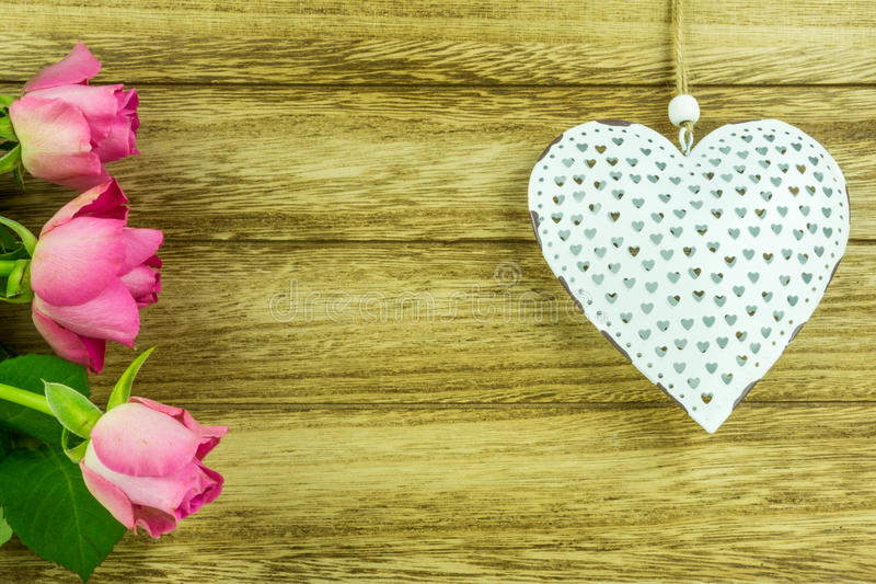 White heart with red roses. On a rustic wooden table royalty free stock image