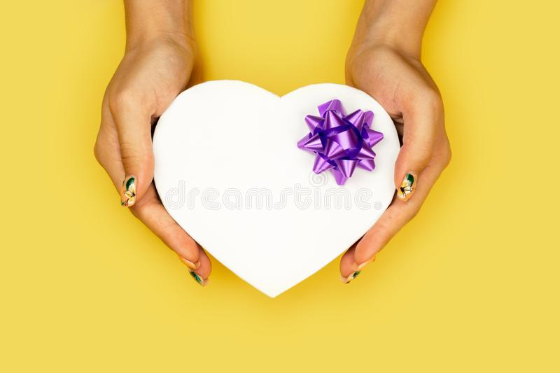 White heart shape gift box in woman hands  on yellow background with copy space. stock image