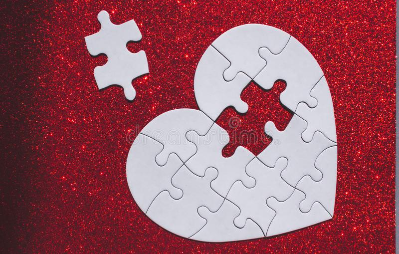 White heart shaped puzzle on red sparkle background. White heart shaped puzzle with missing part on red sparkle background royalty free stock photography