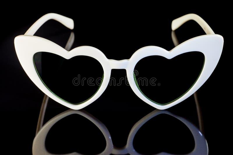 White heart shaped sunglasses on a black background. Accessory, collection, cute, design, elegance, element, eye, eyeglasses, eyesight, eyewear, fashion stock photos