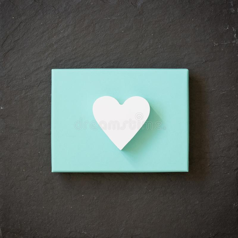White heart on a turquoise color box on black background. Valentine`s day. Present. Gift stock photos