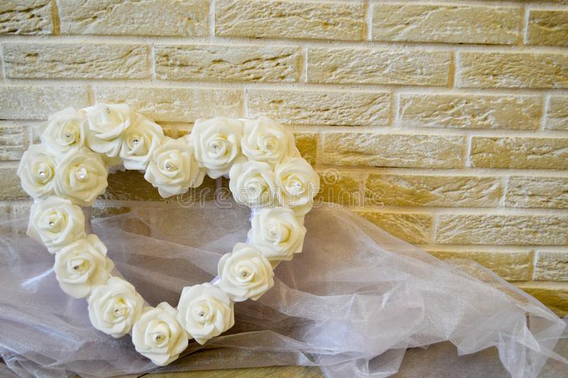 White heart with white roses and diamonds. Background of beige bricks. White transparent fabric royalty free stock image