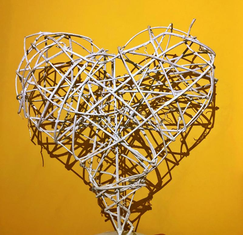 White heart from the wire on a yellow background. Barb, barbed, isolated, metal, fence, old, rusty, abstract, symbol, beautiful, barbwire, border, boundary stock images
