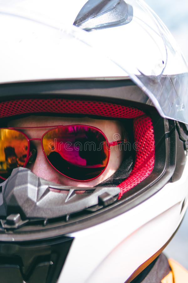 White helmet and red sunglasses. Biker girl wearing a motorcycle outfit, protective clothing, equipment, close-up portrait. stock photo