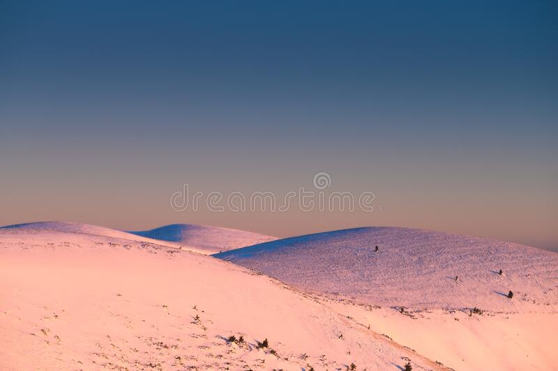 White hills covered by snow under blue sky, edit space. High Quality Photo royalty free stock image