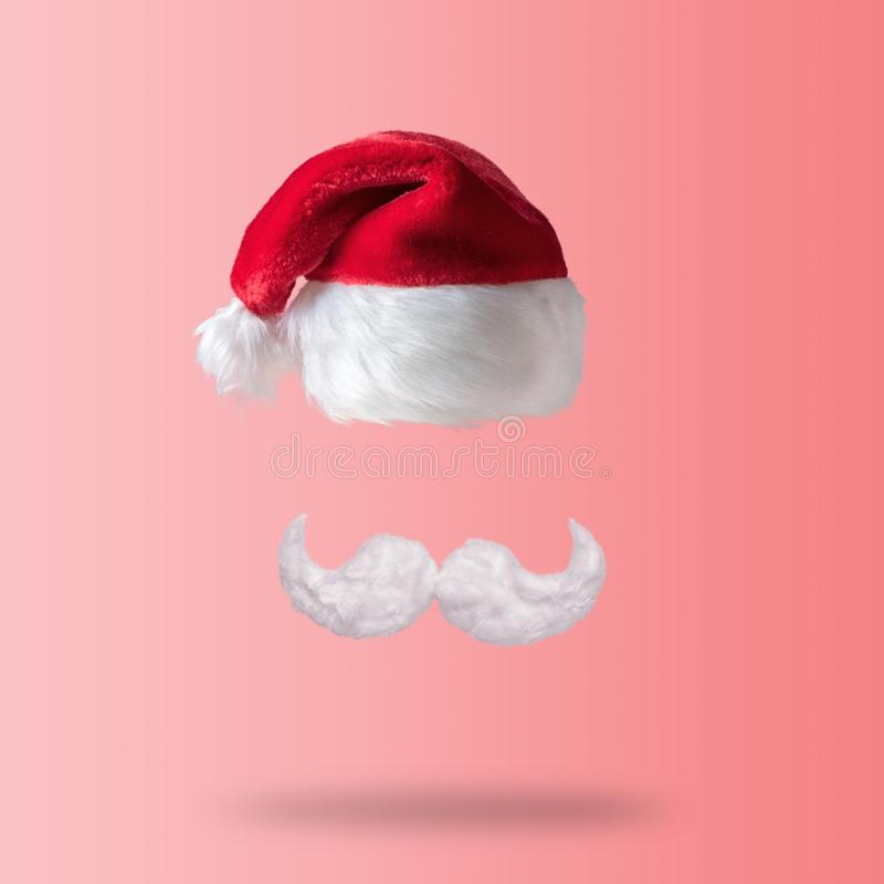 White hipster mustache and hat of Santa Claus on pink background. New Year or Christmas minimal concept stock photography