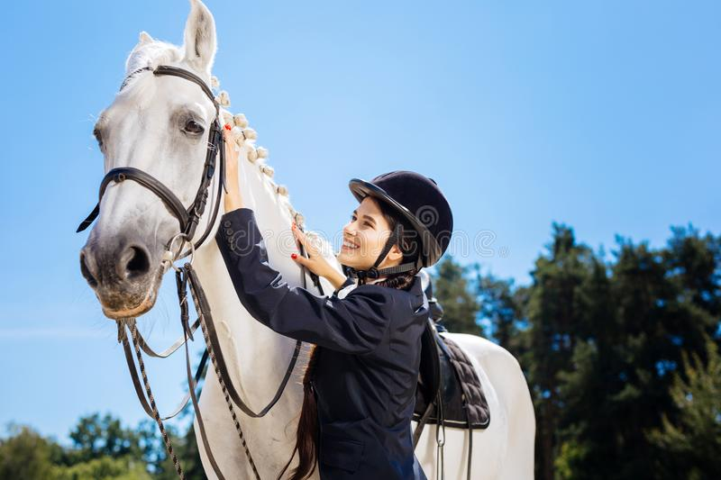 Appealing horsewoman smiling while looking at her gentle white horse. White horse. Appealing dark-haired horsewoman smiling broadly while looking at her gentle royalty free stock photo