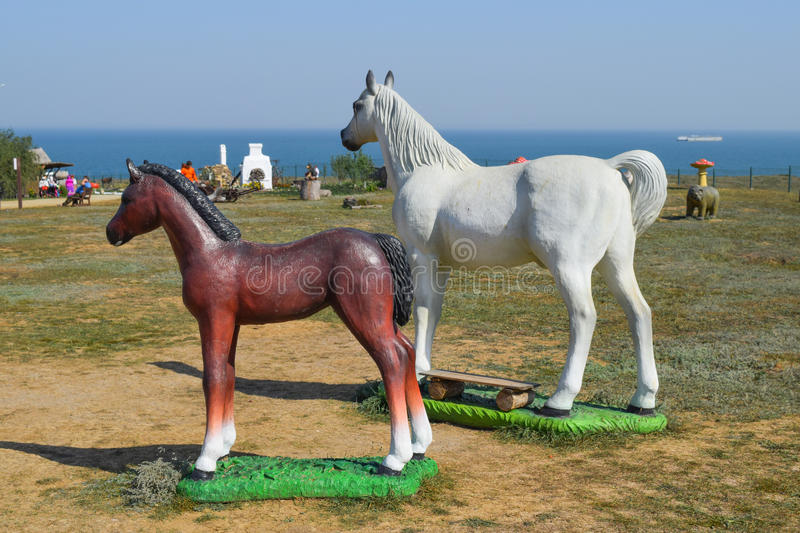 White horse and brown foal. Figures of horses made of plastic on the lawn stock image