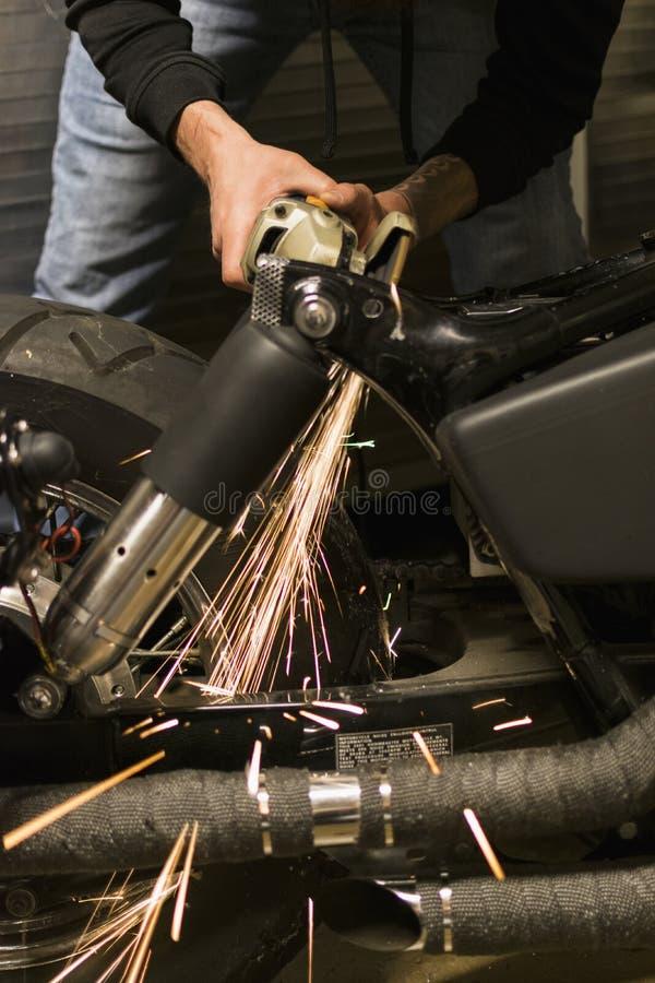 White hot metal sparks from grinder bouncing off bike frame stock image