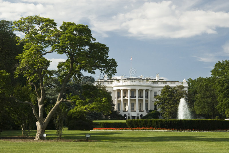 The White House. With fountain, perfect grass garden and sunning blue sky with clouds - Washington DC 2007 royalty free stock photo
