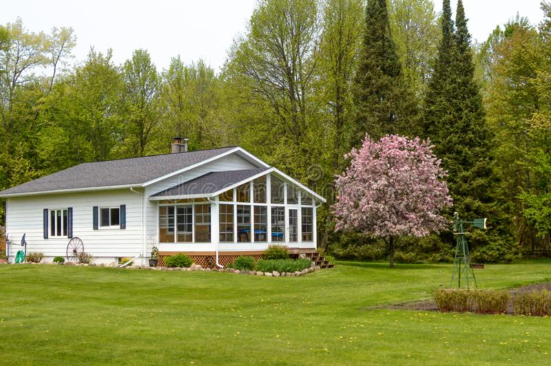 White House with Blooming Crab Apple Tree. A white house with a large screened porch and a blooming crab apple tree in the Northwoods of Wisconsin royalty free stock photography