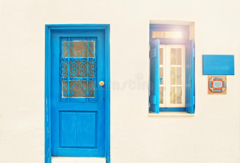 White house with blue door and open window on sunny day stock images