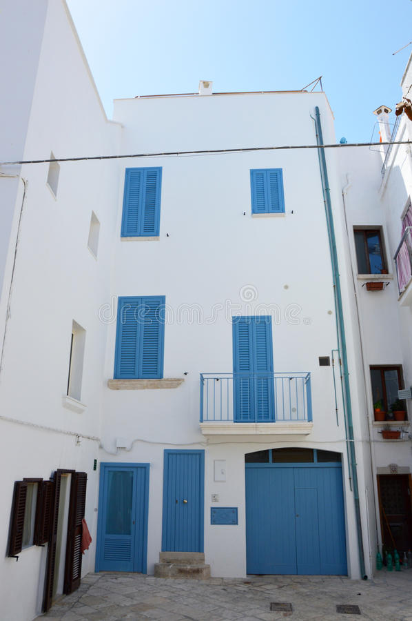 White house with blue windows and doors in Polignano a mare old town, Apulia, Italy stock photography