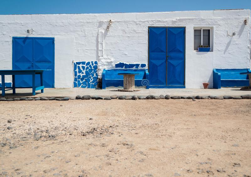 White house with blue windows and doors and sand floor. Fuerteventura, Canary Islands. royalty free stock photography