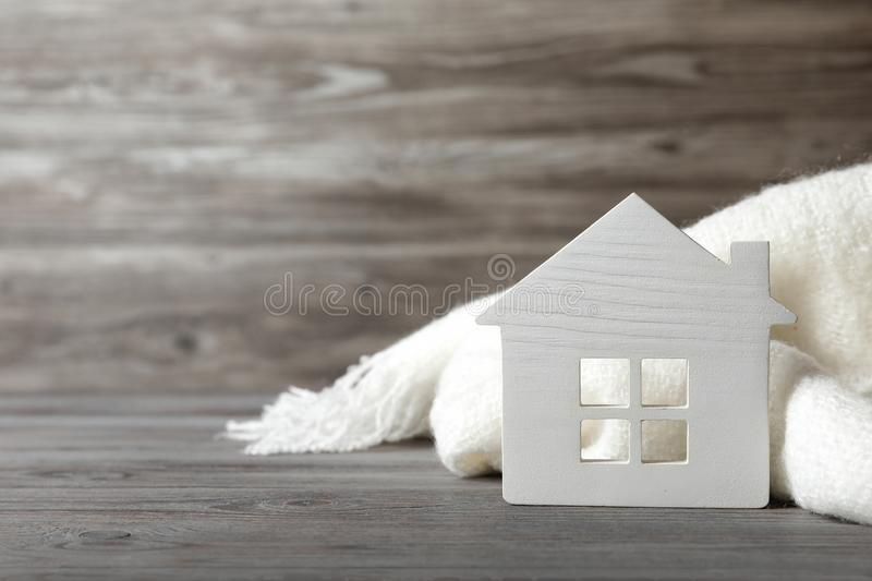 White house model and scarf on wooden table. Heating efficiency. White house model and scarf on wooden table, space for text. Heating efficiency royalty free stock images