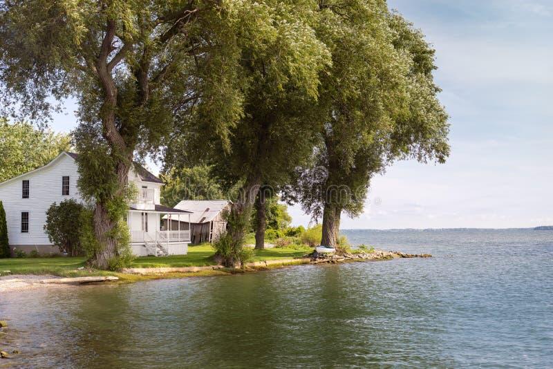 White house on a shaded lake shoreline. A white farmhouse shaded by giant trees along a lake shoreline royalty free stock photography