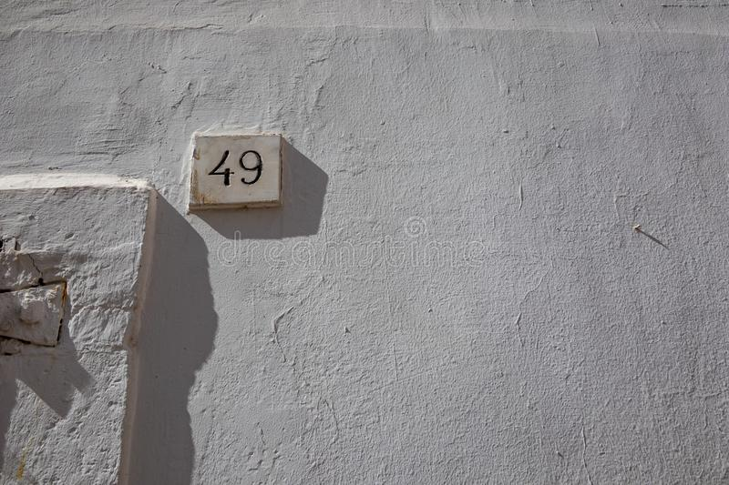 White street number forty-nine 49. White house street number forty-nine 49 carved into marble parallelepiped full with black paint, white-washed buildings in stock image