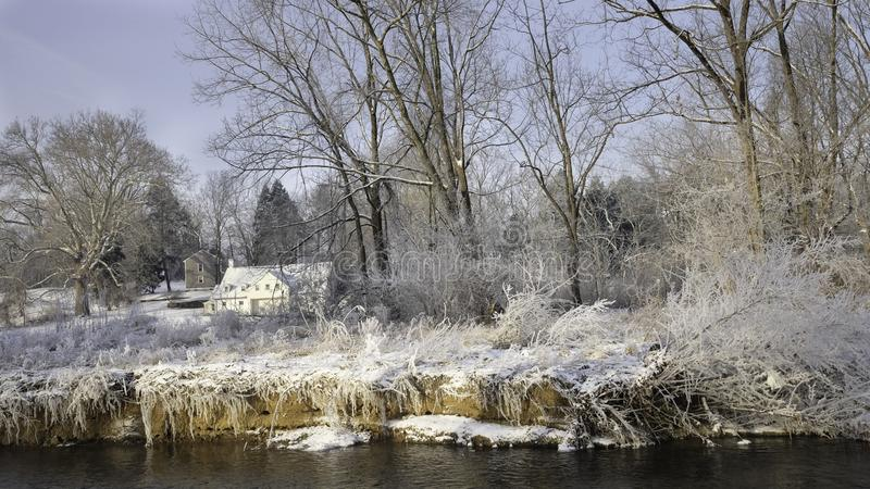 White house in sunlight in distance with snow covered grass and tress on the river bank in front. Chesterbrook PA USA-02 02 2019:White house in sunlight in stock images