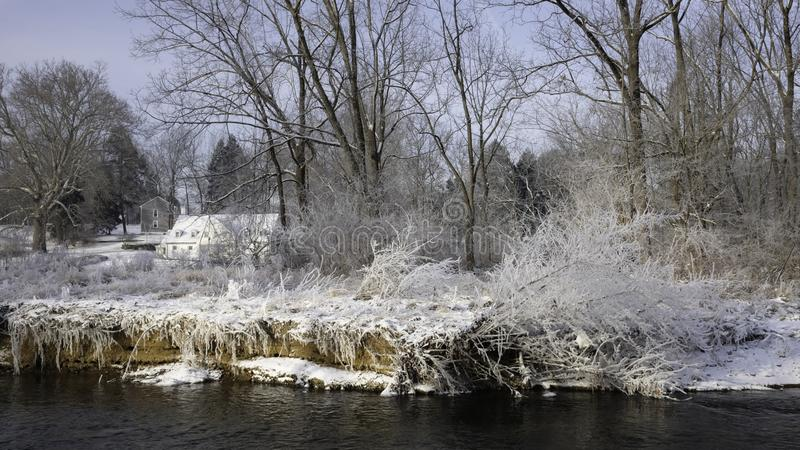White house in sunlight in distance with snow covered grass and tress on the river bank in front. Chesterbrook PA USA-02 02 2019:White house in sunlight in royalty free stock image