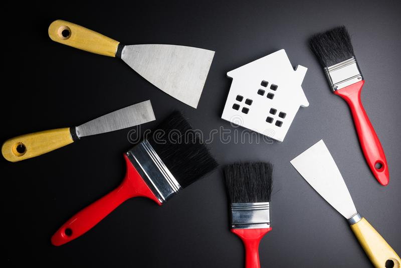 White house toy and paint brush, painters equipment on black background with copy space.Real estate concept, New house concept, F. Inance loan business concept royalty free stock photography