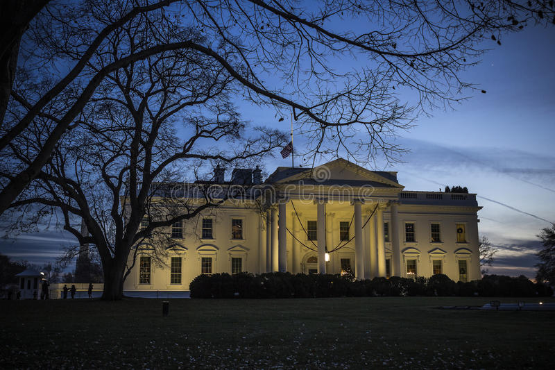 The white house in twilight. The silhouettes from the trees are overgrowing the white house where the flag is put on half due to Nelson Mandela's death stock images