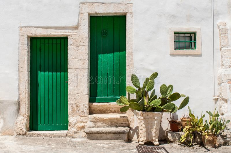 White house wall facade, green door and shutters royalty free stock photography