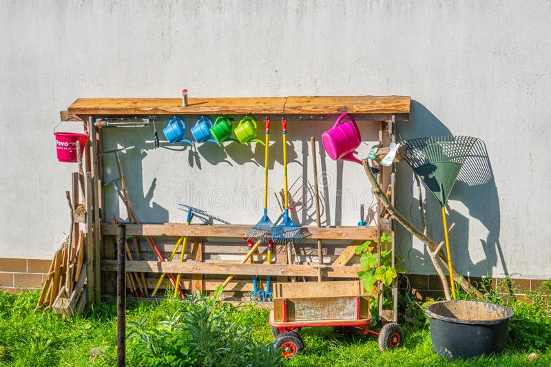 a white house wall in a kindergarten stands a shelf filled with various garden tools for children stock photos