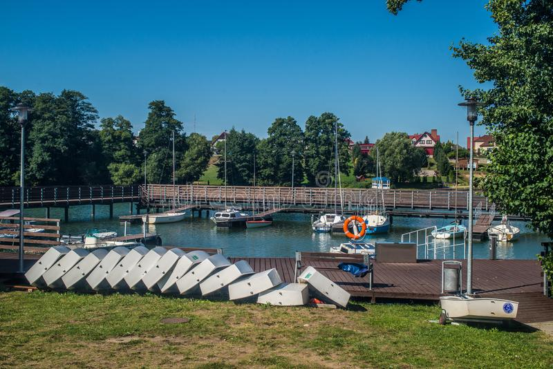 Small Optimist class boat on wharf after regatta. White hulls of small boats of Optimist class used for training sailing of children prepared for transportation royalty free stock images