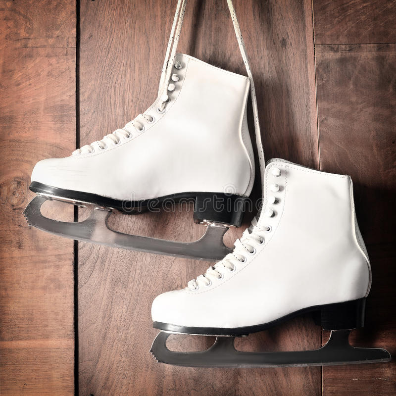 White ice skates for figure skating, hanging on wooden background stock images