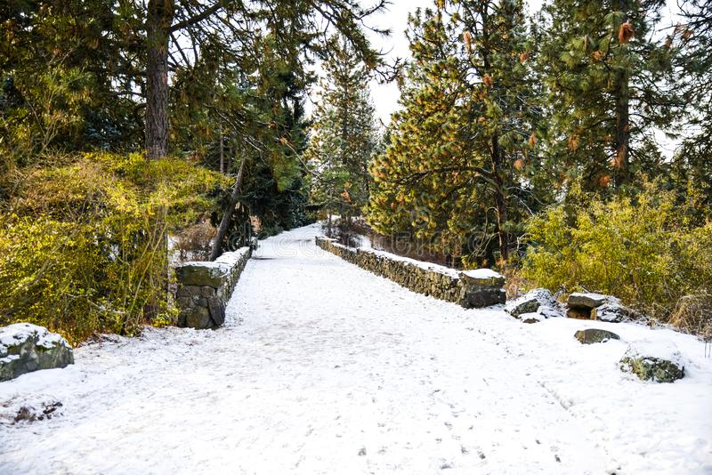 White Icy Snowy Walkway Through A Foot Bridge At A Park In Freezing Winter, Spokane, Washington, United States. Walking through Manito Park in the middle of stock photos