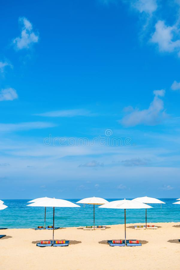 Idollic beach relaxing concept with white parasols on sand. White idillic beach parasol sunshade on sand beach with blue clear sea and a bit cloudy sky on stock photos