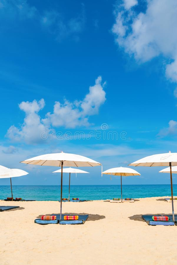 Idyllic beach relaxing concept with white parasols on sand. White idyllic beach parasol sunshade on sand beach with blue clear sea and a bit cloudy sky on royalty free stock photos