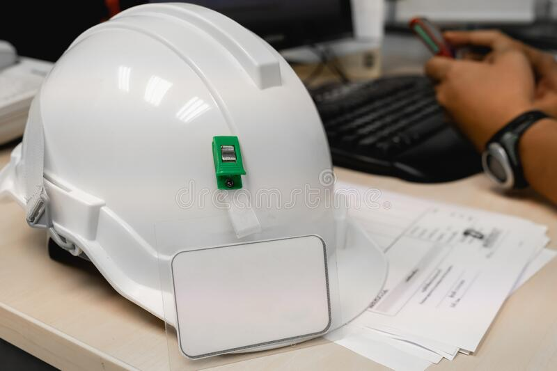 The white industrial helmet is placed in the office on the desk stock photo