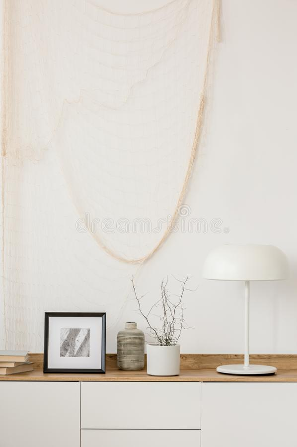 White industrial lamp, photo in frame and plant in pot on wooden console table in elegant living room with white wall. White industrial lamp, photo in frame and stock photos