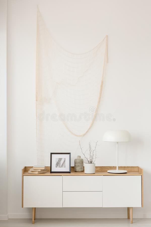 White industrial lamp, photo in frame and plant in pot on wooden console table in elegant living room with white wall. White industrial lamp, photo in frame and royalty free stock photography