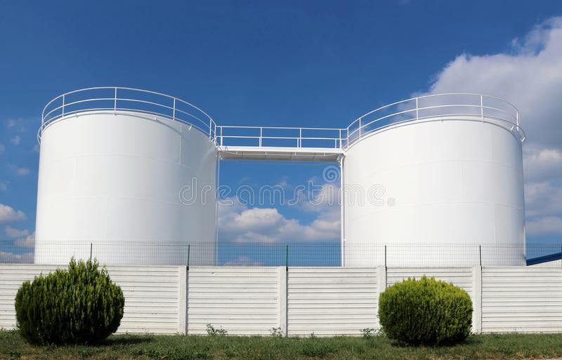 White industrial liquid storage tanks with a white fence in front. Blue sky with fluffy clouds on background stock images