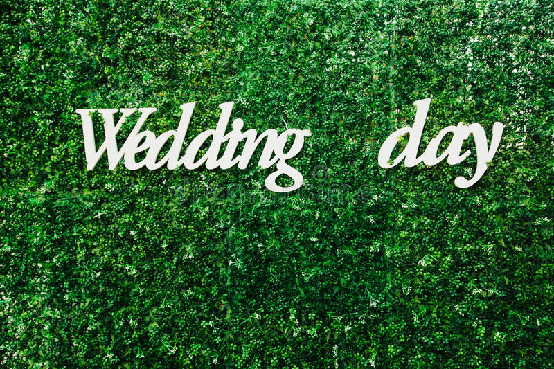 White inscription wedding day on a big green wall. Wooden plaque with the inscription `wedding day` in the area of the wedding celebration royalty free stock photos