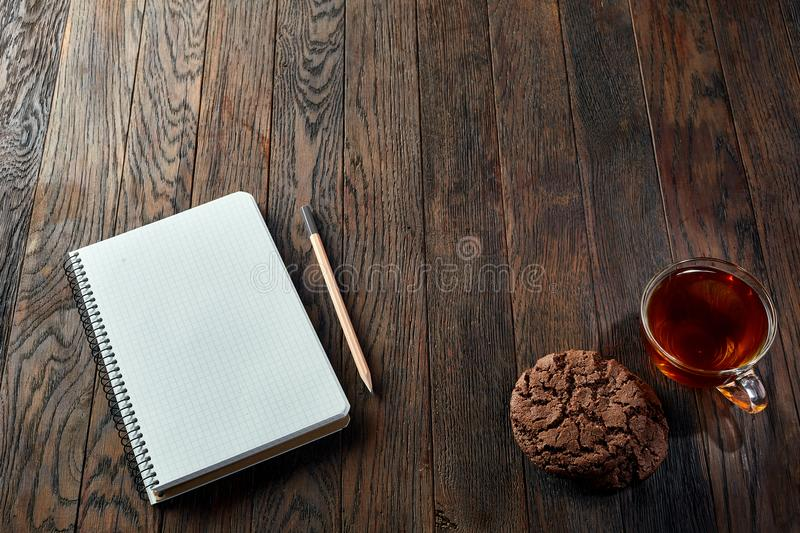 Cup of tea with cookies, workbook and a pencil on a wooden background, top view. A white inside and brown outside porcelain cup of tea with tasty chocolate chips stock images