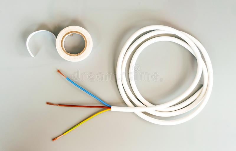 White insulating tape and three-core cable on a gray background royalty free stock photos