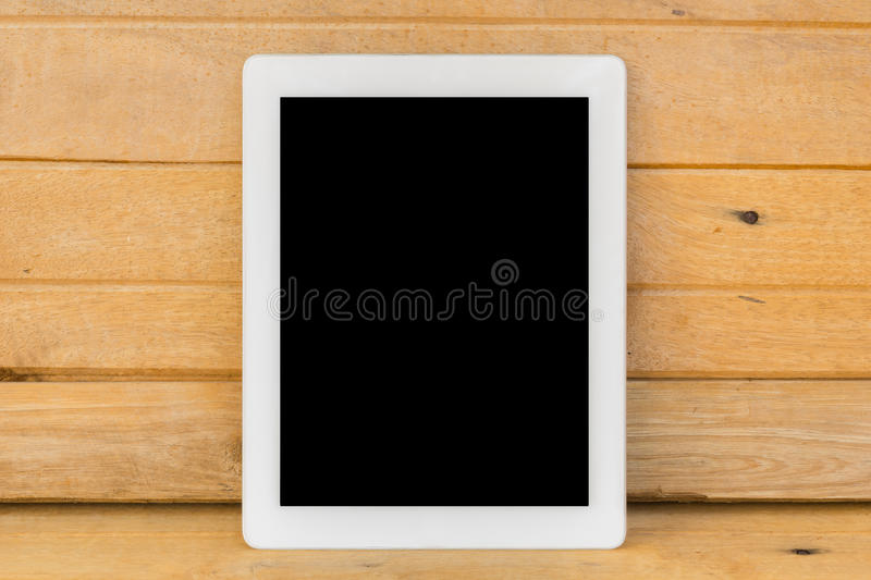 White ipad on brown wood table background royalty free stock photos